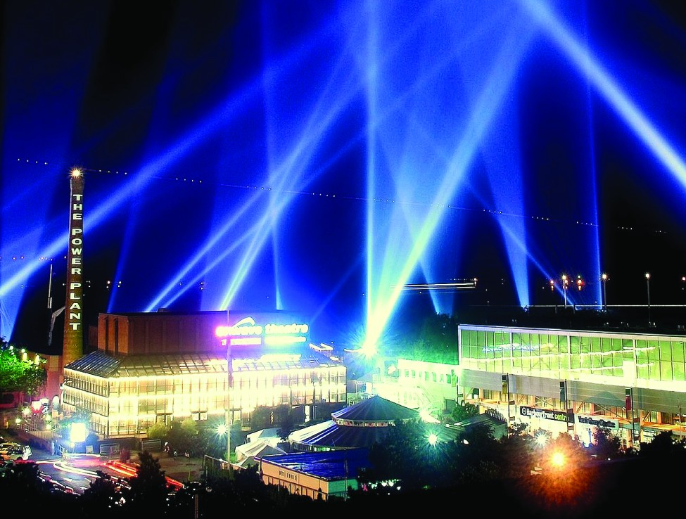 This is a photo of searchlight beams in the night sky of a city scene.