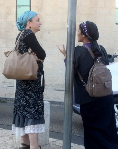 Photo of two women on street talking. Both wear dresses and head scarves.