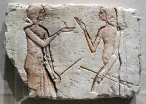 Photo of a stone carving depicting two men holding spears, facing each other