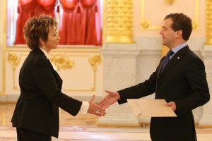Photo of a man and woman shaking hands in an elegant room. Both wear suits, and the man is holding an envelope.