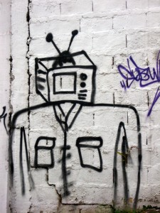 Photo of graffiti in black paint on a white wall, depicting a human figure with a television for a head