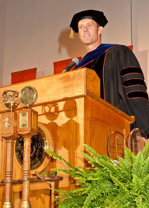 Photo of a man in a graduation gown standing at a lectern
