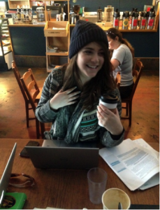 Photo of a girl seated in a coffee shop, smiling, holding a coffee cup and her other hand is resting against her chest.