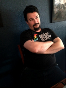 Photo of a guy leaning back in a chair, arms folded across his chest, with a smirk on his face.