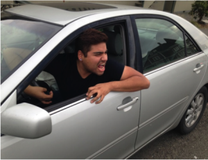 Photo of a guy leaning out a driver's side window of a car, yelling