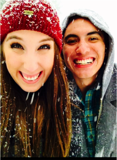 Photo of young man and woman wearing winter gear, in the snow, smiling into the camera