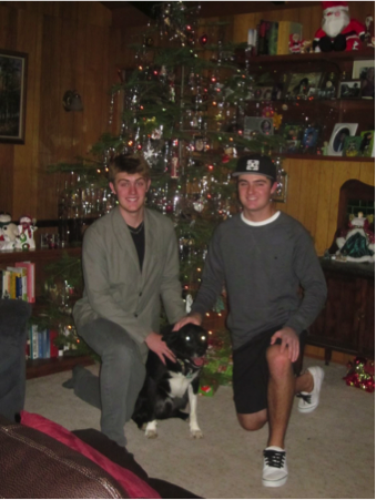 Photo of two teenage boys kneeling in front of a Christmas tree, with a dog between them