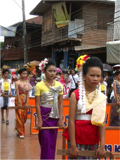 Photo of women marching in a parade in Thailand, holding banners.  They wear traditional Thai clothes and flowers in their hair.