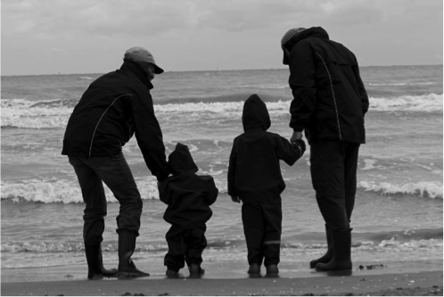 Photo of two men and two children on the beach in jackets.