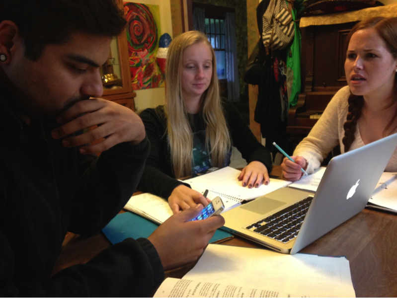Photo of three students sitting at a table together, working on a project
