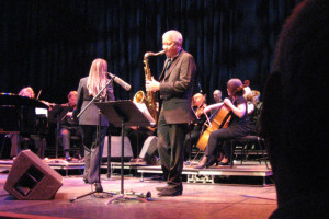 Band on stage performing. Prominent is a saxophone player.