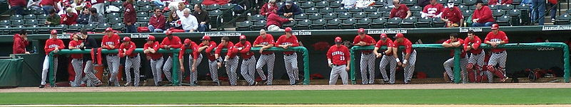 Photo of a group of baseball players hanging over the dugout wall, watching the game