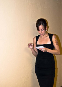 Photo of woman in evening dress staring at notecards in a hallway