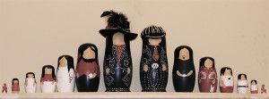 Photo of two sets of nesting dolls, lined up with the largest dolls in the middle, leading out to the smallest at each end