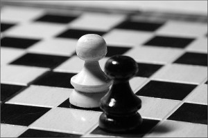 Black and white photo of two pawns, one white and one black, diagonal from one another on a chessboard