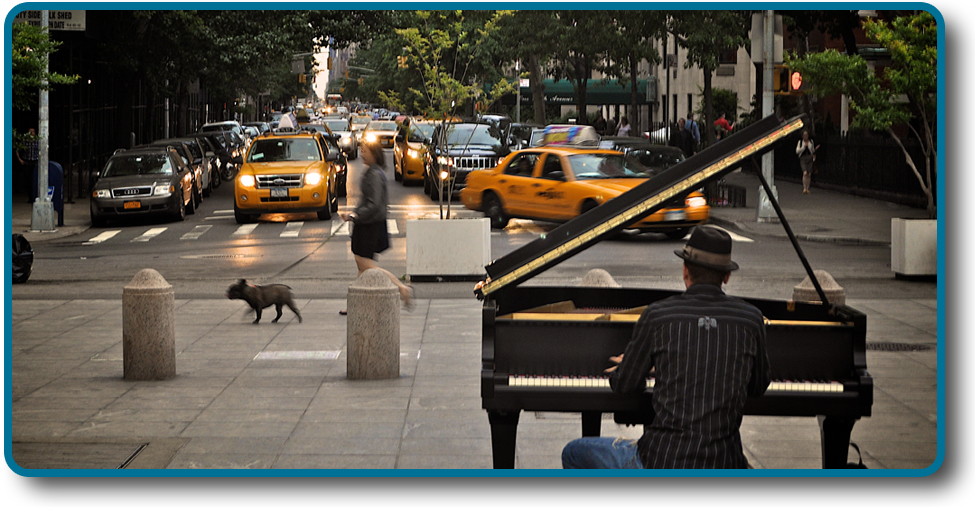 A person playing a piano on the sidewalk near a busy intersection in a city.