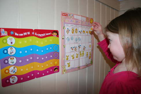 A child placing stickers on a chart hanging on her wall.