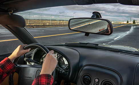 A photograph shows a person driving a car.