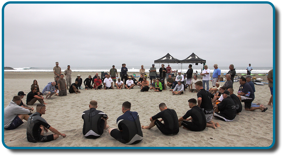 This photo depicts a large group of people sitting in a circle on the beach.