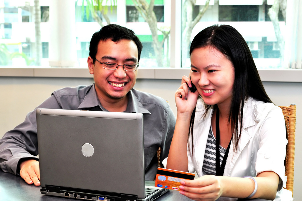 Photo of a man and woman looking at a computer, smiling. The woman is talking on the phone and holding a credit card.