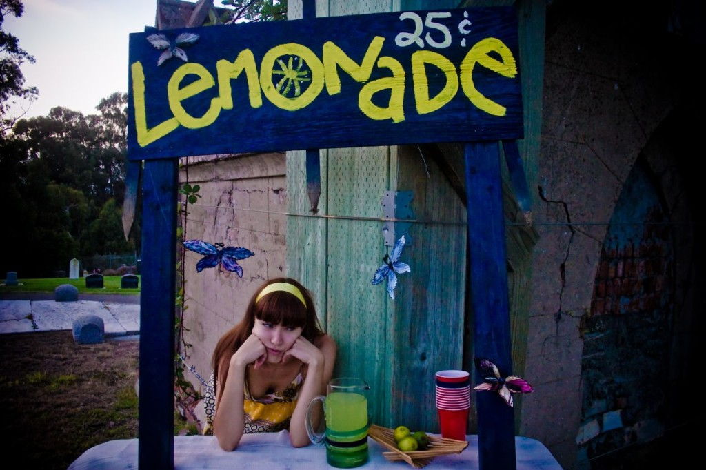 Photo of a colorful lemonade stand set up in a cemetery. The discourage young woman running the stand is shown with her head in her hands.
