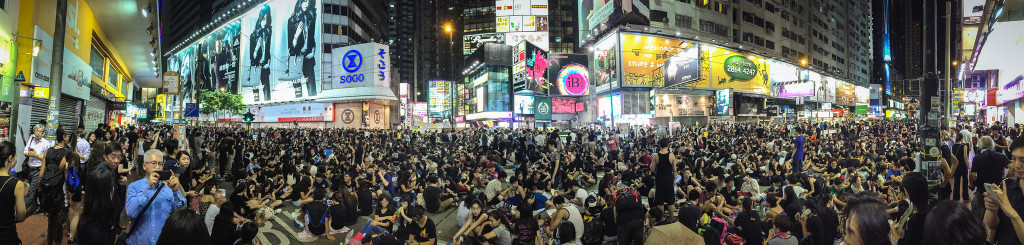 Panoramic color photo of busy Hong Kong intersection (not unlike Time Square in NYC) showing brightly lit digital ads and hundreds of people sitting in the street and on the sidewalks.