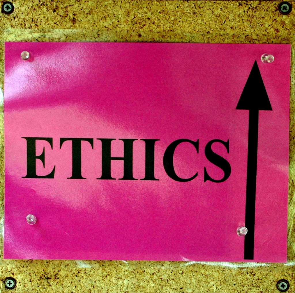 Bright pink laminated paper thumbtacked to a cork board. The pink sign contains the word ETHICS in black; to the right of the word is a black arrow pointing up.