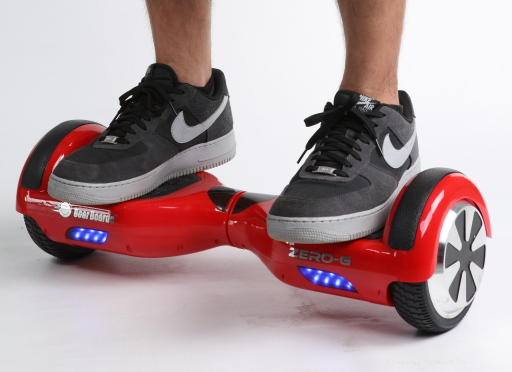 Red, self-balancing, two-wheeled scooter shown with someone wearing Nike sneakers standing on it.