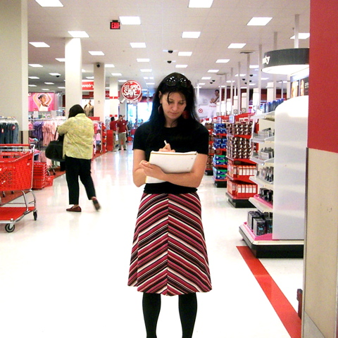 A woman holding and writing in a notebook stands inside a Target store. Other shoppers are in the background.