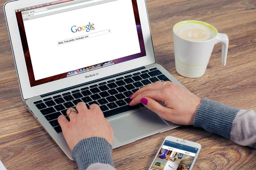 Photo of a woman's hands on a laptop keyboard; the homepage of GOOGLE is on the screen.