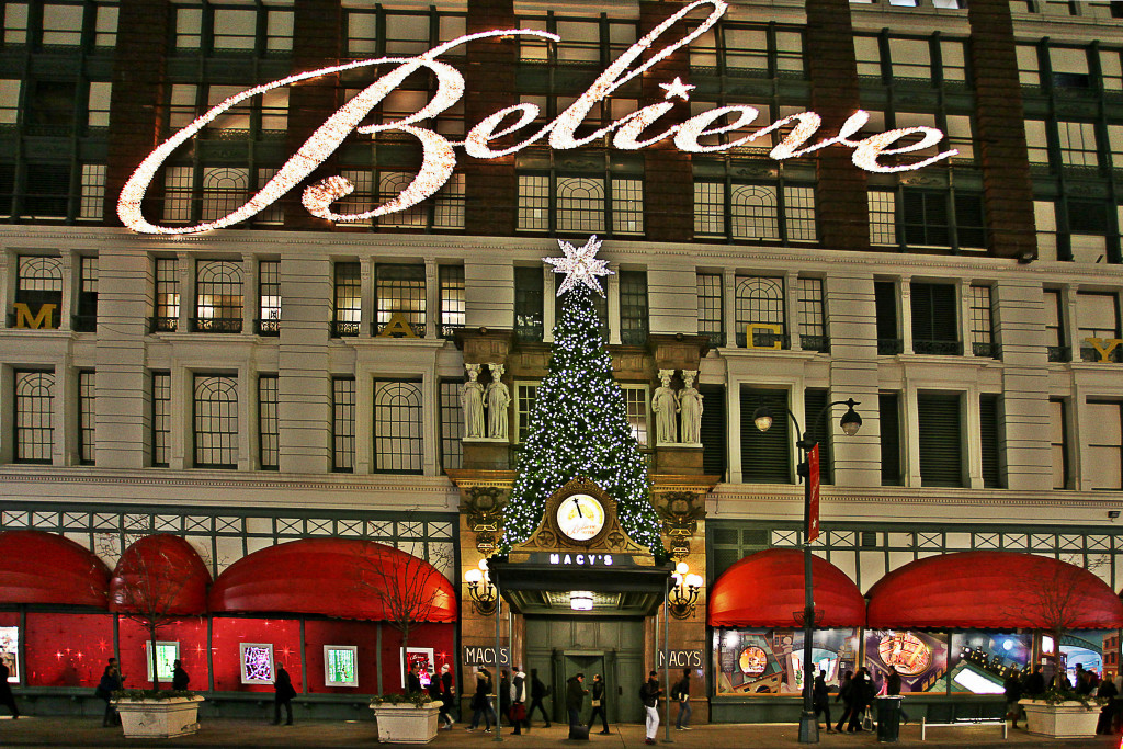 """Front view of Macy's department store in New York City, decorated at Christmastime with a large white lighted sign spelling the word """"Believe."""""""