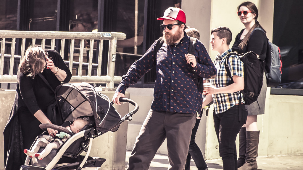 Man with a full beard wearing a red hat pushes a stroller with a baby inside. A woman is checking on the child and talking on her cell phone. Two young people are walking in the background.