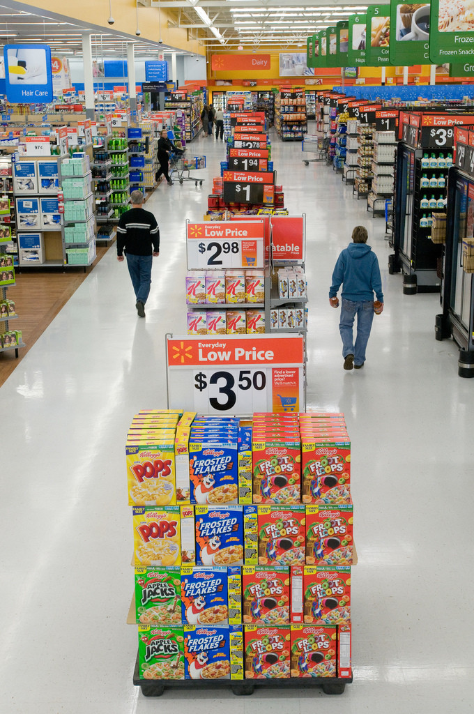 Photo of a shopping aisle in Walmart. Large center-aisle displays of breakfast cereal are in the foreground. Three shoppers are in the background.