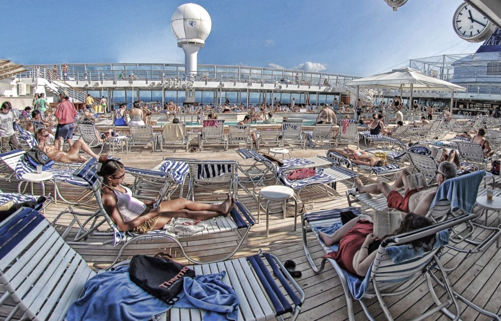 Digitally altered photo with a deck-top view of cruise ship, showing many sunbathers on lounge chairs around a large pool. The distorted colours give the picture a quiet, frozen quality.