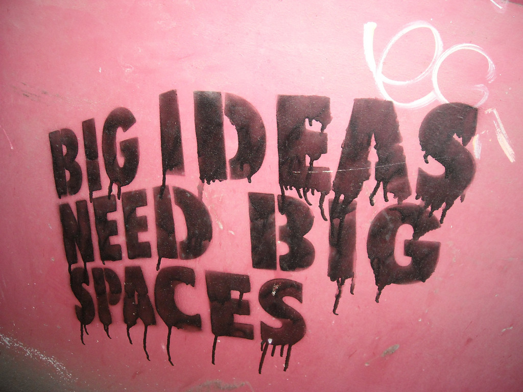 """Pink wall with black block letters that read """"Big Ideas Need Big Spaces."""""""