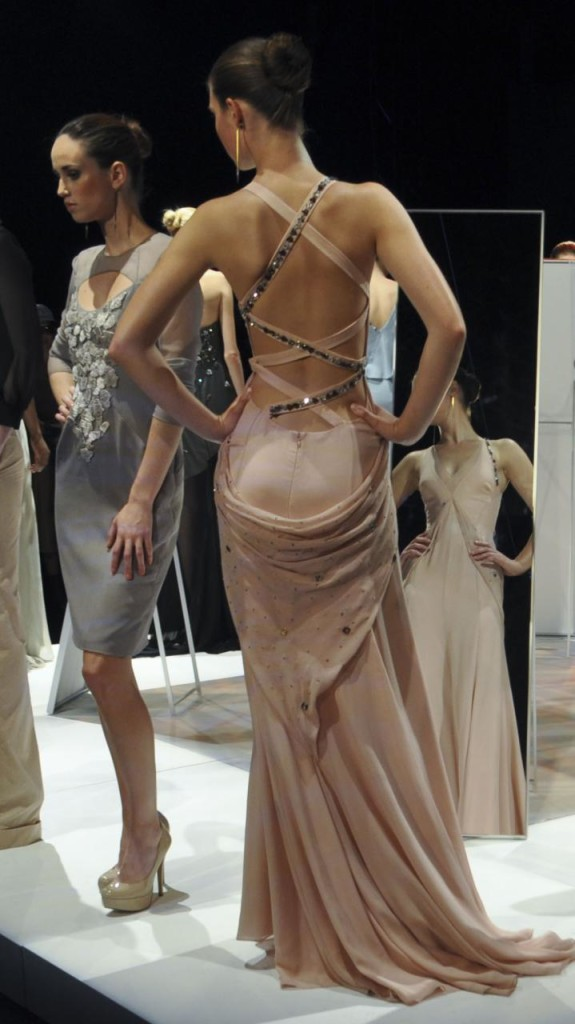 Three runway models wearing gowns pose in front of mirrors.