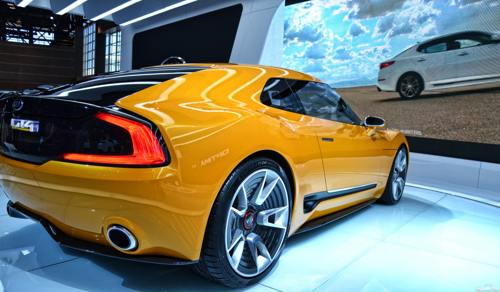 Photo of a yellow KIA GT4 Stinger sports car in a show room.