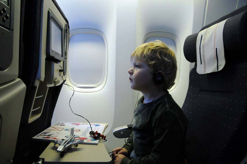 Young boy is shown in profile while seated in an airplane. He's watching something on the video screen in front of him.