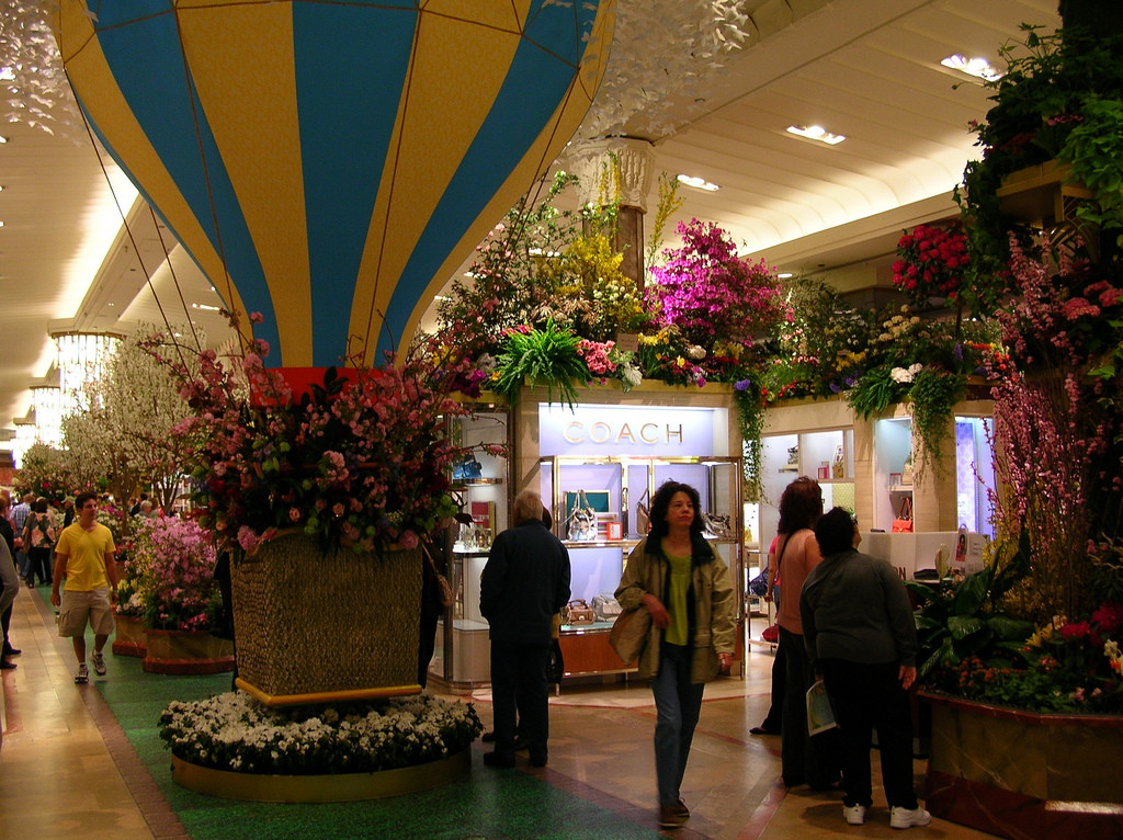 Photo of main floor of Macy's department store, decorated with flowers and a large hot-air balloon and several shoppers.