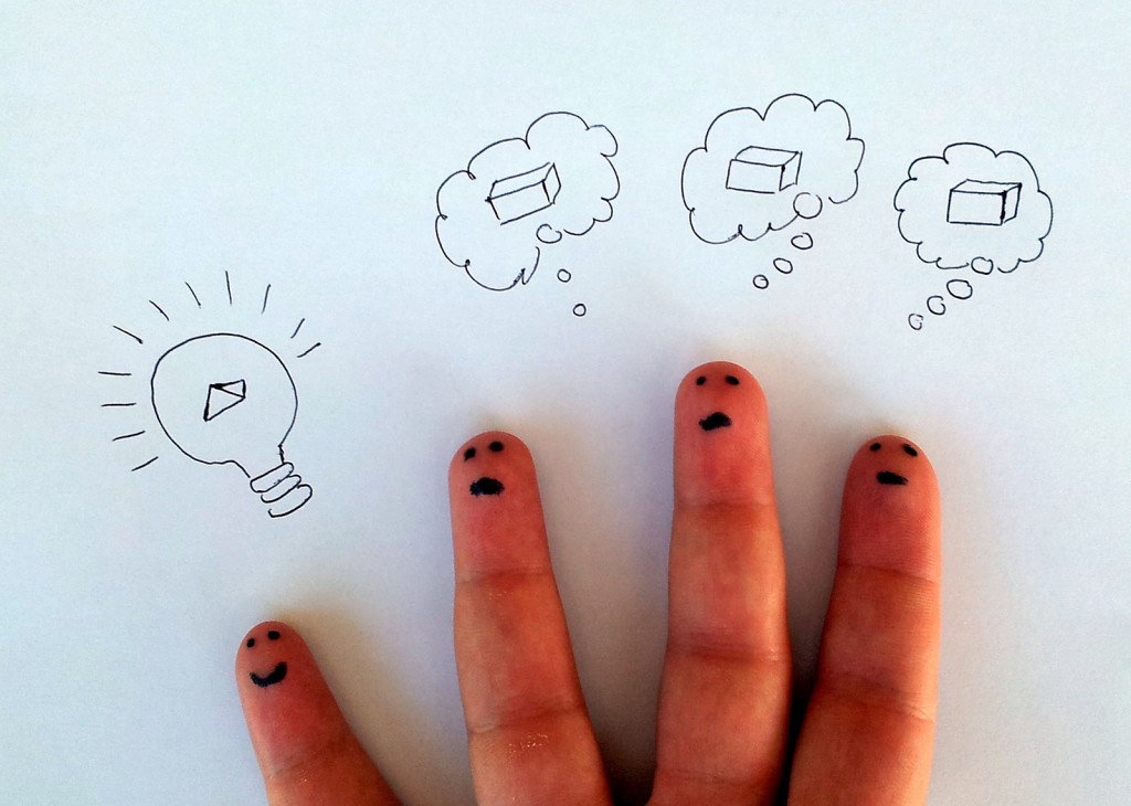 """Photo of four fingers, each with a face drawn on the fingertip. Above the pinky is a drawing of a lightbulb with a pyramid inside. Above each of the three other fingers is a """"thought bubble"""" with a picture of a box inside. The lightbulb finger is apparently """"thinking outside the box,"""" unlike his finger peers."""