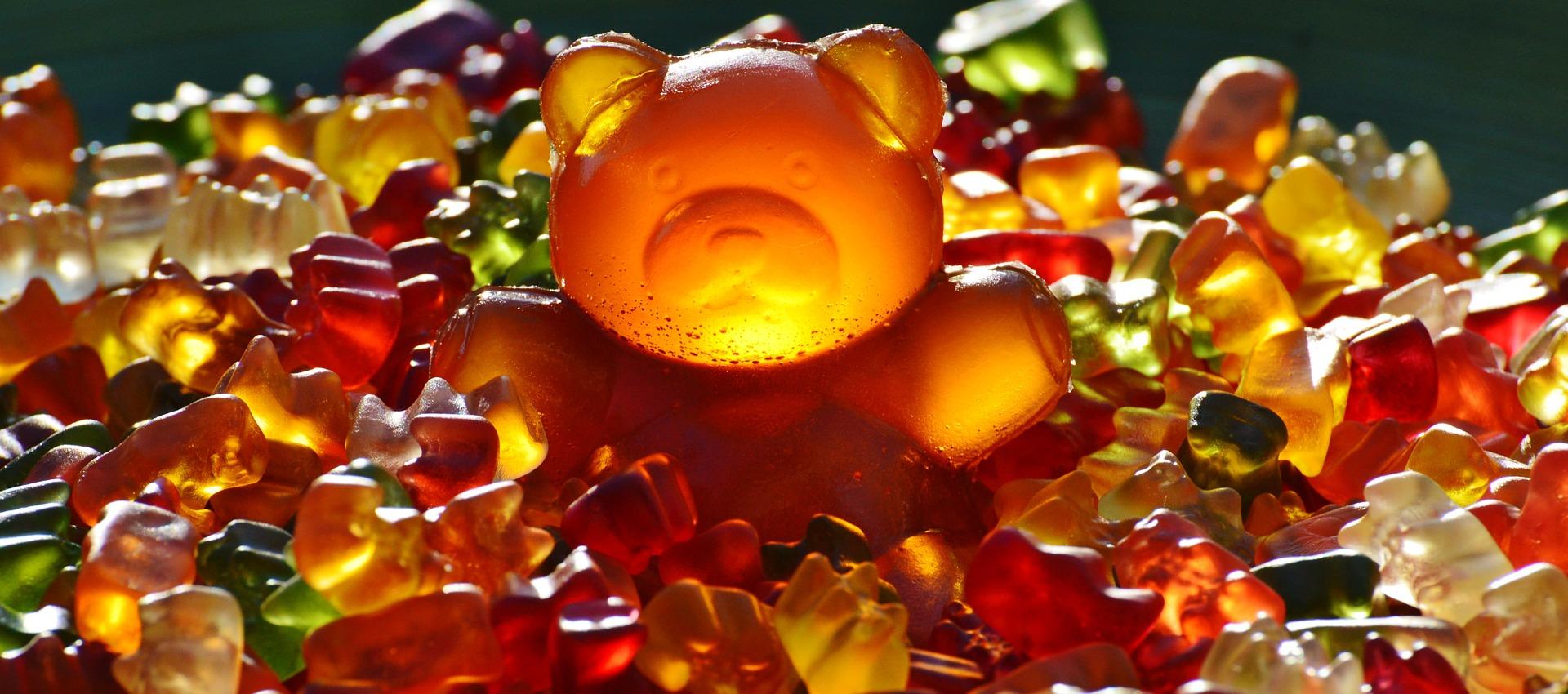 An enormous gummy bear surrounded by tiny gummy bears.
