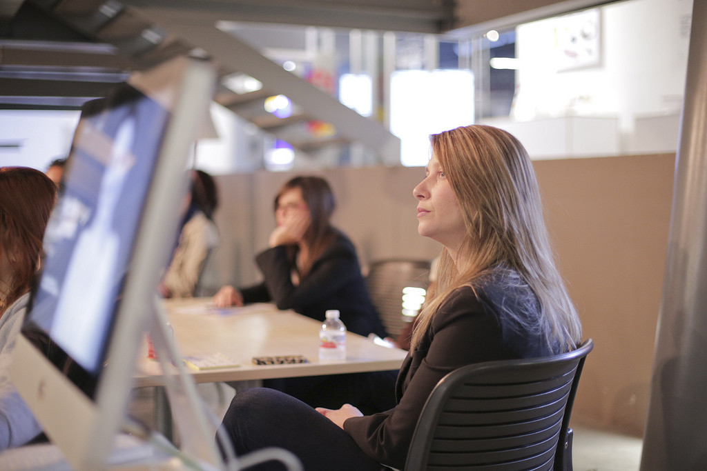A woman listening intently in a meeting.