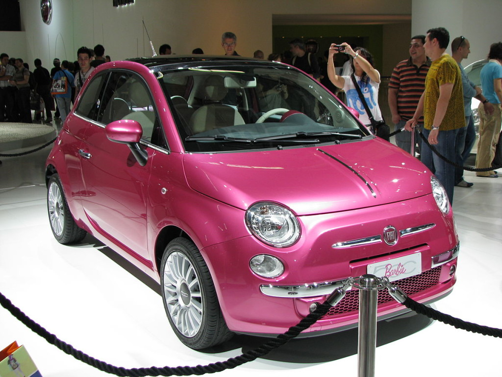 A pink two-door car on a brightly lit car show floor.