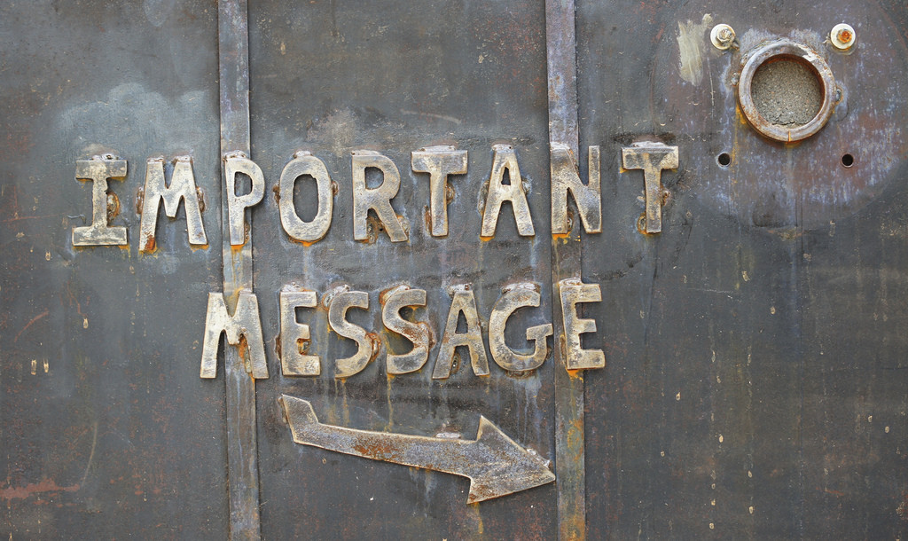 """A sign on a metal door reads """"Important Message"""" with an arrow pointing to the right."""