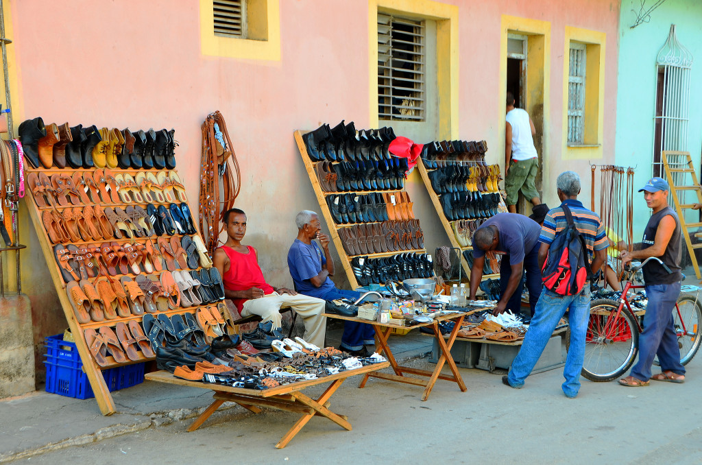 Tables on the street filled with shoes available for sale on the street. A few people peruse the shoes.