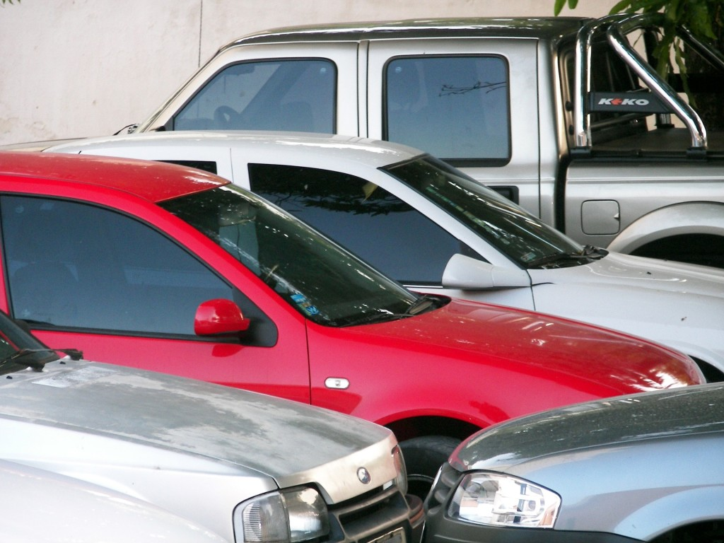 Cars packed tightly in a parking lot.