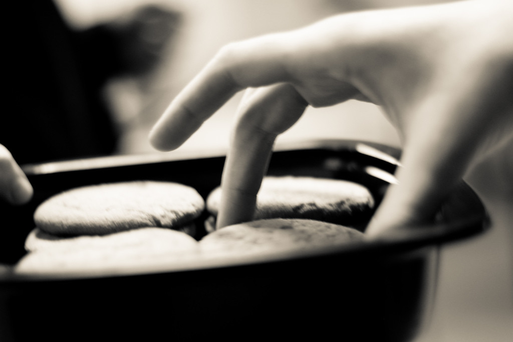 A hand plucking cookies out of a platter.