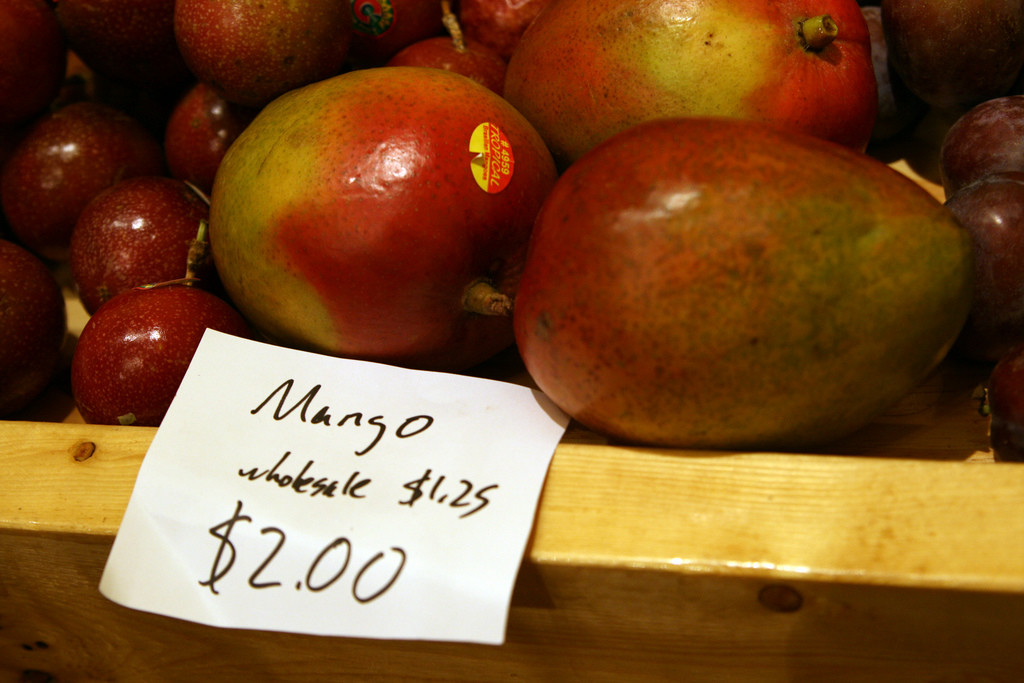 A basket of mangoes at the supermarket. A sign reads mango $2, wholesale $1.25.