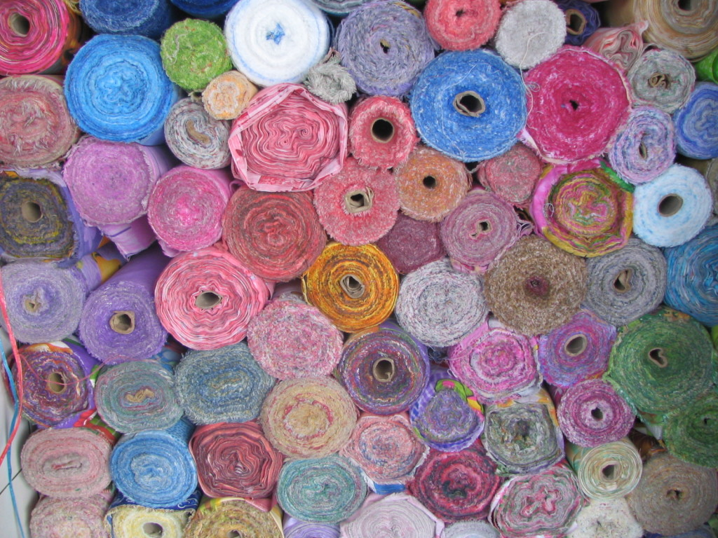 A stack of colorful rolled-up carpets.