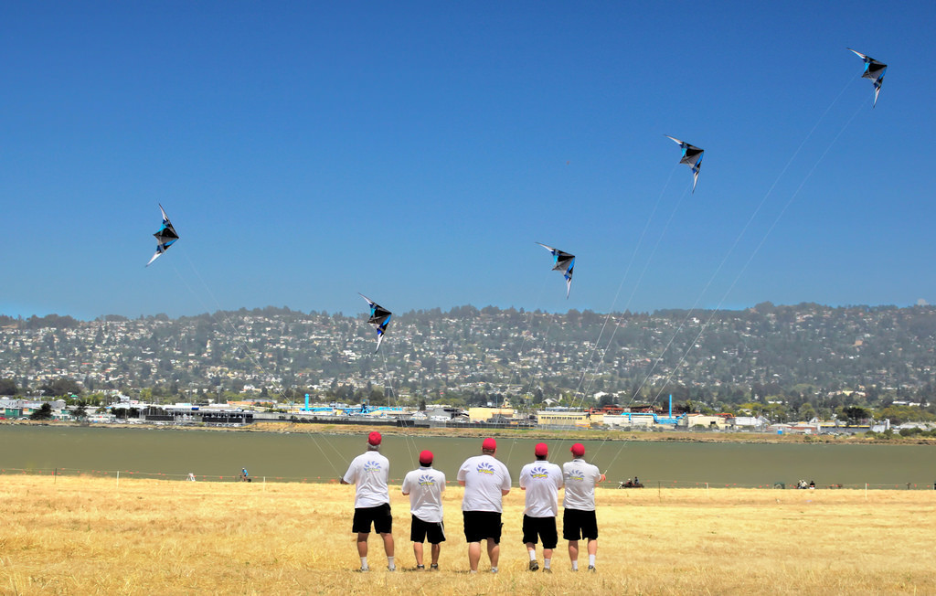 Five men wearing identical hats, shirts, and shorts. They are each flying identical kites.